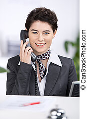 Friendly receptionist talking on a telephone