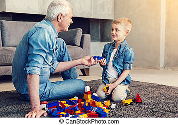 Friendly relatives playing bricks together