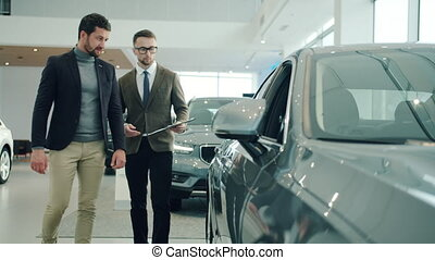 Friendly sales manager in car dealership talking to male ...