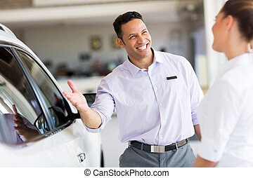 salesman selling car to a customer in showroom - friendly...