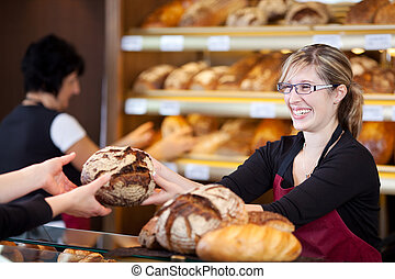 friendly saleswoman in bakery passing bread
