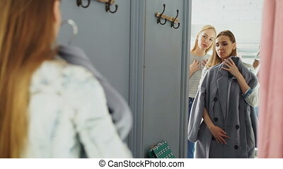Friendly saleswoman is helping female customer to choose a coat. Cheerful shopper is standing in fitting room in front of large mirror and fitting garment.