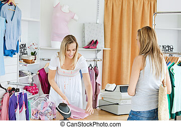 Friendly saleswoman packing clothes in a bag