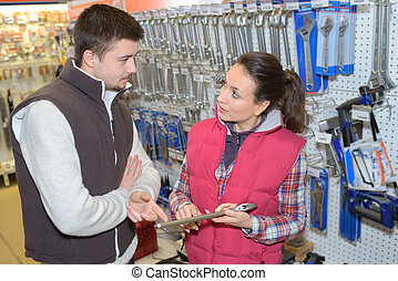 friendly saleswoman selling to customer in hardware store