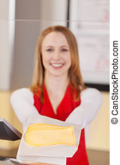 Friendly saleswoman showing sliced cheese