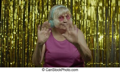 Friendly positive senior old blond woman waving hands looking at camera with toothy smile, saying hi, greeting. Elderly stylish lady grandma in headphones on golden background in studio. 6k footage