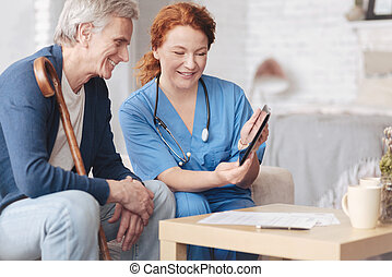 Friendly senior patient and nurse looking tablet computer