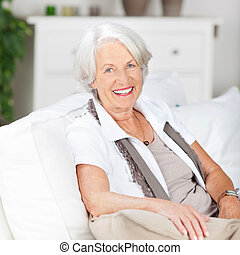 Friendly senior woman relaxing at home