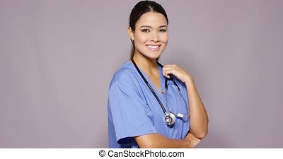 Friendly sincere young woman doctor or nurse standing...