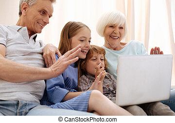 Friendly smart children using laptop for calling parents