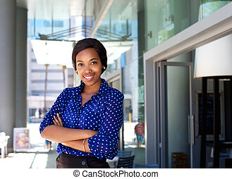 Friendly smiling business woman standing outside in the city