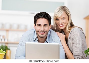 Friendly smiling couple with a laptop computer
