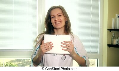 Friendly smiling doctor woman with tablet computer on video conference.
