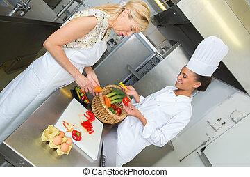 friendly smiling female chefs preparing food on restaurant kitchen