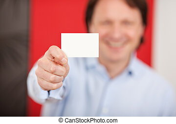 smiling man in a shop showing white card