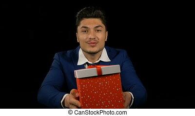 Friendly smiling man opening a big gift box