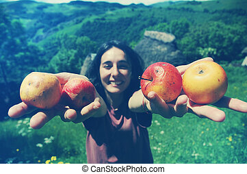 Friendly smiling woman holding apples in her hands
