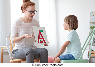 Friendly speech therapist and boy - Young boy sitting on...