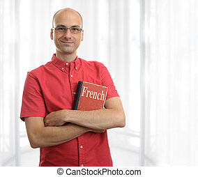 friendly student man with French book. Education concept