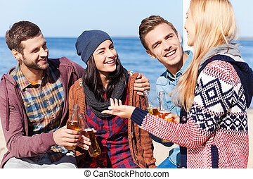 Friendly talk. Four happy friends talking to each other and smiling while sitting on the beach and drinking beer