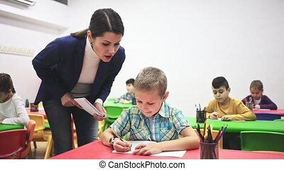 Friendly teacher woman helping boy during lesson in ...