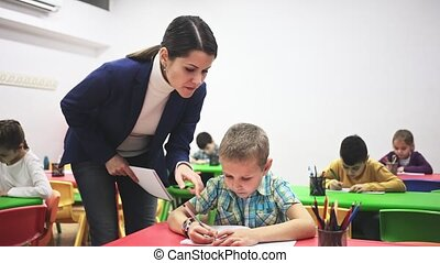 Young female teacher working with pupils in classroom at elementary school