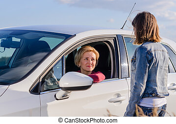 Friendly teenage girl talking with a female driver -...