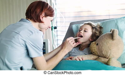 Friendly woman doctor examining small girl in bed in ...