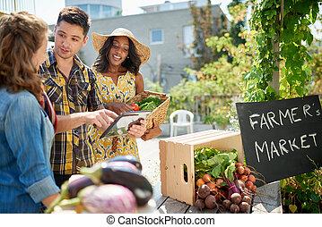 Friendly woman tending an organic vegetable stall at a ...