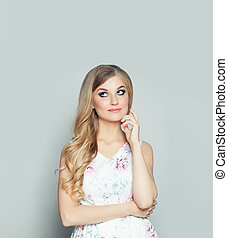Friendly woman thinking and looking up on white background with copy space