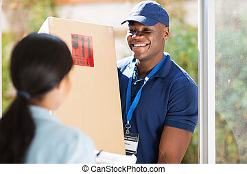 young african american delivery man delivering a package - ...