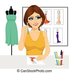 friendly young brunette fashion designer thinking concept holding a pencil and drawing dress design sketches