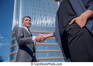 friendly young businessman shaking hands with his business partner.