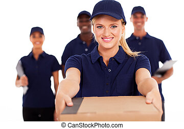 friendly young delivery woman presenting parcel with...