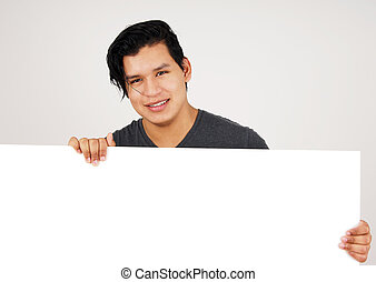 Friendly young latino man holding white sign