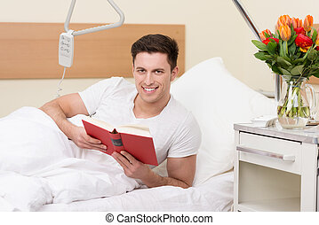 Friendly young man reading in a hospital bed