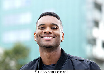 Friendly young man smiling outdoors
