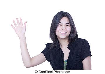 Friendly young teen girl waving hello or goodbye