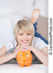 Friendly young woman with her piggy bank