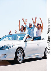 Friends and road trip. Group of young happy people enjoying road trip in their white convertible while raising arms and smiling