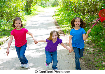 Friends and sister girls running in the forest track happy