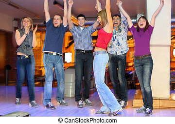 Friends are glad and lift hands upwards for successful throw of girl in center