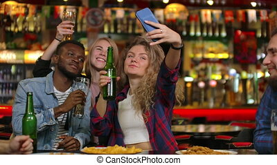 Friends are taking selfie with smartphone in bar. Young people are posing, laughing and talking. Beer bottles and. Friends are taking selfie with smartphone in.