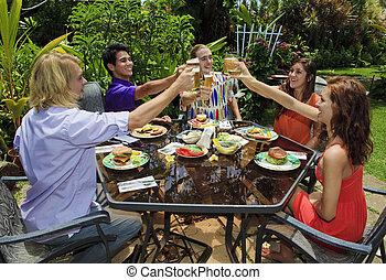 friends at a backyard bar-b-que in hawaii raising their ...