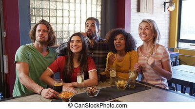 Friends at the bar in a pub having fun - Front view of a ...