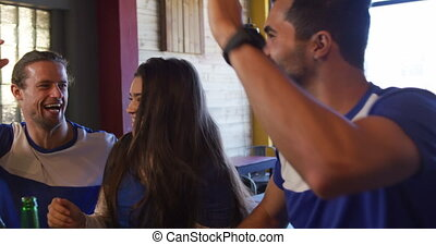 Front view of a mixed race couple, Caucasian man and woman, at the bar in a pub during the day, watching a sports game, the woman kissing her partner on a cheek, celebrating together, high fiving, in slow motion