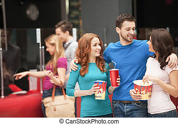 Friends at the cinema. Cheerful young people talking at the...