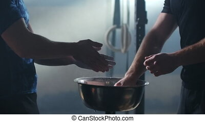 Friends Athletic adults applying talcum powder to hands. Cheerful athletic adults talking while applying talcum powder to hands before doing intense workouts requiring a firm grip