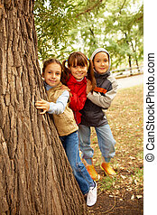 Friends behind tree - Portrait of happy kids looking at...