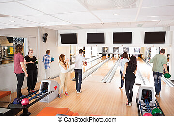 Friends Bowling in Club - Group of young friends bowling in...